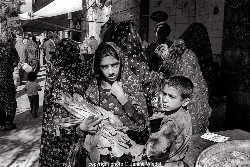 Group of young women in chadors carrying vegetables in Tehran street Iran 1970s