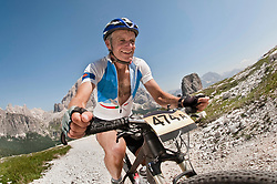 Senior man riding uphill in mountain bike race, Cinque Torri, South Tyrol, Italy