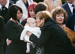 © licensed to London News Pictures. 08/09/2011. Brize Norton, UK..Baby rose, daughter of Sergeant Barry Weston receiving a kiss before the body of the Commando Royal Marine passes the memorial in Carterton after arriving at RAF Brize Norton for the first time. Sgt Weston was killed on August 30 while leading a patrol near the village of Sukmanda in southern Nahr-e Saraj, Helmand province. Photo credit: Ben Cawthra/LNP