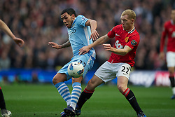 MANCHESTER, ENGLAND - Monday, April 30, 2012: Manchester City's Carlos Tevez in action against Manchester United's Paul Scholes during the Premiership match at the City of Manchester Stadium. (Pic by David Rawcliffe/Propaganda)