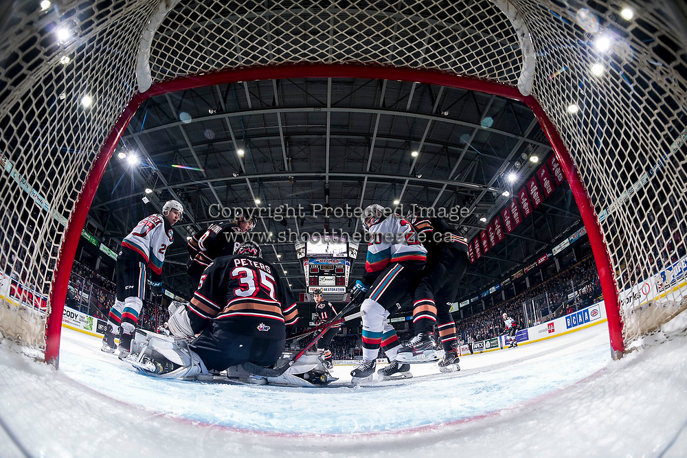 KELOWNA, BC - FEBRUARY 17: Brayden Peters #35 of the Calgary Hitmen defends the net as Matthew Wedman #20 of the Kelowna Rockets digs for the puck at Prospera Place on February 17, 2020 in Kelowna, Canada. (Photo by Marissa Baecker/Shoot the Breeze)
