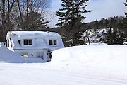 This pretty little two-story home on the shore of Lac La Belle is carrying quite a snow load. The late winter first floor view is now an 8 foot tall snow bank.