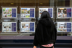 © Licensed to London News Pictures. 02/03/2021. London, UK. A woman view a display of properties for sale in an estate agents window. Chancellor of the Exchequer, Rishi Sunak will deliver the Spring Budget to Parliament on Wednesday, 3 March 2021. It is expected that the government will announce plans to create 'Generation Buy', aimed at helping people with a small deposit to buy a property. Mortgage lenders will be able to provide 95% loans to some 3,000 people each month on properties worth up to £600,000. Photo credit: Dinendra Haria/LNP