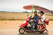 14 MARCH 2013 - HOUAY XAI, LAOS:   A family on a motor scooter in Huay Xia, Bokeo province, Laos. The umbrella has been modified to give sun protection to everyone on the motor scooter. PHOTO BY JACK KURTZ