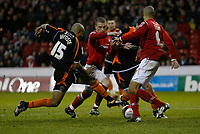 Photo: Richard Lane/Richard Lane Photography. Nottingham Forest v Blackpool. Coca Cola Championship. 13/12/2008. Joe Garner (C) tries to squeeze through but Alex Baptiste (L) clears. Nathan Tyson (R) in attendance