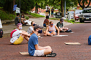 "30 JULY 2020 - DES MOINES, IOWA: People sit in the road on Forest Drive in front of the Governor's Mansion. About 45 high school students from across Des Moines marched from downtown to the Governor's Mansion to protest Iowa Governor Kim Reynolds' proclamation ordering Iowa schools to reopen to in person classes despite the COVID-19 pandemic. The students stood in front of the mansion and chanted before staging a ""die  in"" in the street. The Governor's order mandates in person instruction rather than on line or a mix of on line and in person. Several school districts have indicated that they will disregard the Governor's orders and reopen with a hybrid system or mostly on line. The Governor will allow districts to apply for a waiver if the Coronavirus (SARS-CoV-2) infection rate is more than 15% in their community.     PHOTO BY JACK KURTZ"