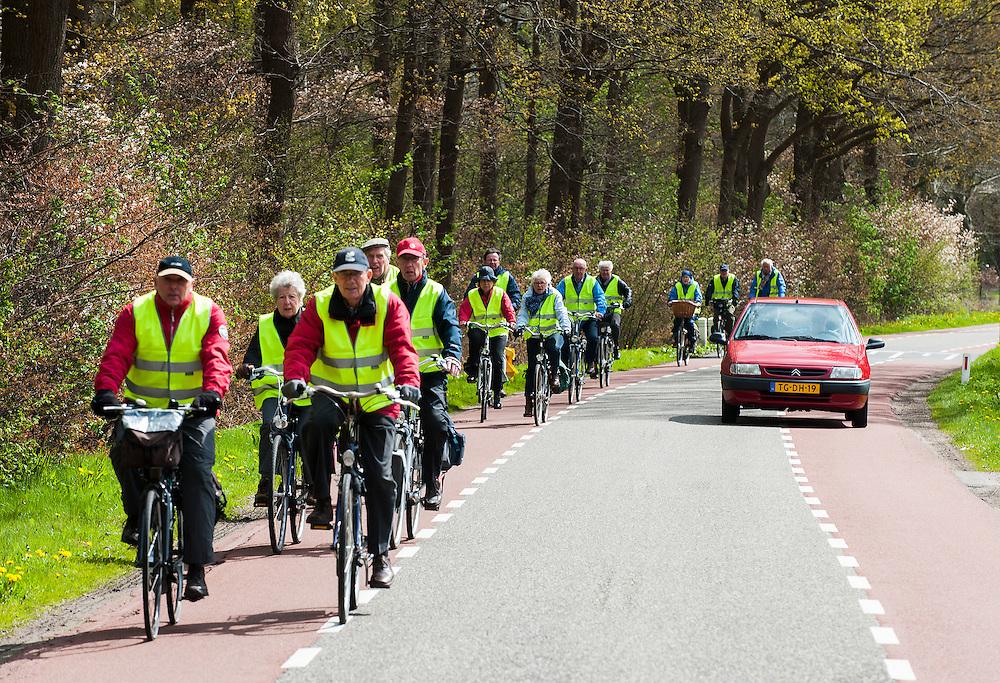 Nederland, Leusden, 19 april 2012.Een groep ouderen fietst over landelijke weggetjes zonder fietspad. Het is een excursie, want er is begeleiding, en de oude fietsers hebben gele hesjes aan voor de veiligheid. .Foto(c): Michiel Wijnbergh