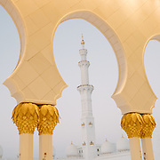 Views through golden archways of the famous Sheikh Zayed Grand Mosque at sunset.