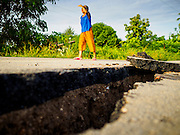 14 JULY 2015 - THAILAND: A woman walks along a damaged road in Pathum Thani province. The road bed collapsed because of subsidence. The drought that has crippled agriculture in central Thailand is now impacting residential areas near Bangkok. The Thai government is reporting that more than 250,000 homes in the provinces surrounding Bangkok have had their domestic water cut because the canals that supply water to local treatment plants were too low to feed the plants. Local government agencies and the Thai army are trucking water to impacted communities and homes. Roads in the area have started collapsing because of subsidence caused by the retreating waters. Central Thailand is contending with drought. By one estimate, about 80 percent of Thailand's agricultural land is in drought like conditions and farmers have been told to stop planting new acreage of rice, the area's principal cash crop.       PHOTO BY JACK KURTZ