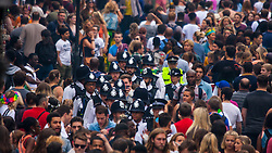 London, August 30th 2015. A group of police officers make their way through the crowd as revellers enjoy day one of the Notting Hill Carnival.