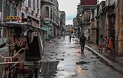 A Pedicab travels through Centro Habana after a heavy rain.