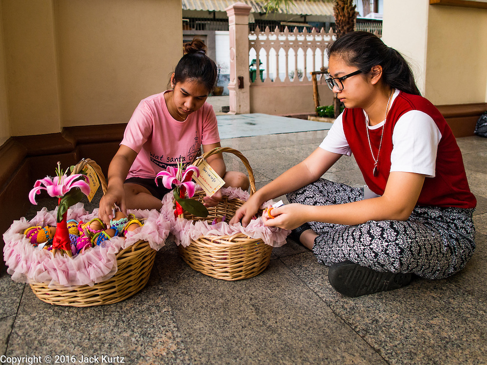 27 MARCH 2016 - BANGKOK, THAILAND: Girls sort Easter eggs they gave to parishioners at Santa Cruz Church in Bangkok on Easter Sunday. Santa Cruz was one of the first Catholic churches established in Bangkok. It was built in the late 1700s by Portuguese soldiers allied with King Taksin the Great in his battles against the Burmese who invaded Thailand (then Siam). There are about 300,000 Catholics in Thailand, in 10 dioceses with 436 parishes. Easter marks the resurrection of Jesus after his crucifixion and is celebrated in Christian communities around the world.      PHOTO BY JACK KURTZ