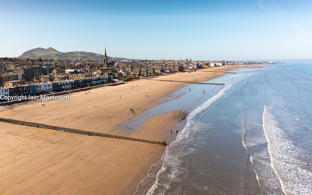 Portobello, Scotland, UK. 3 April 2021. Easter weekend crowds descend on Portobello beach and promenade to make the most of newly relaxed  Covid-19 lockdown travel restrictions and warm sunshine with uninterrupted blue skies. Pic; Aerial drone view of Portobello beach which looks rather quiet at the Eastern end.  Iain Masterton/Alamy Live News