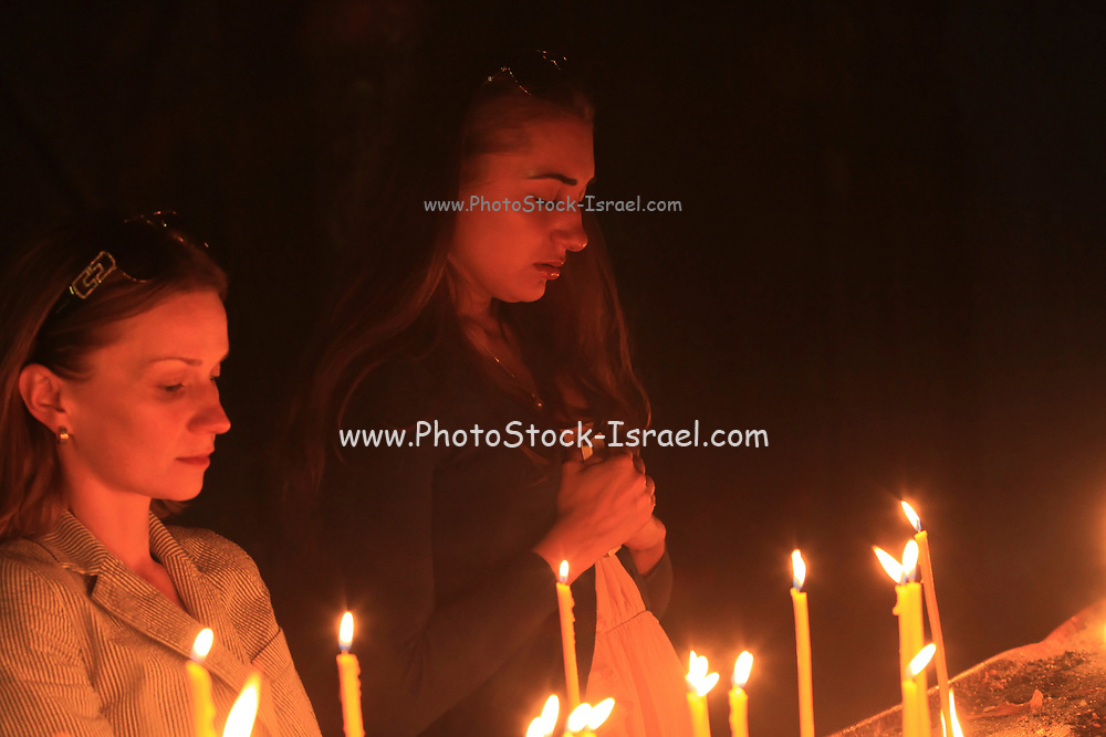 portrait of women faces lit by candle light praying in a church