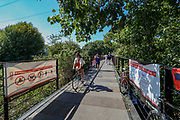 """People enjoy cycling over the """"Friends Bridge"""" of the River Lea in East London as the hot weather hit Britain on Friday, Aug 7, 2020, as the UK could see record-breaking temperatures with forecasters predicting Friday as the hottest day of the year. (VXP Photo/ Vudi Xhymshiti)"""