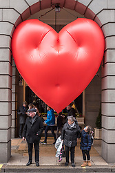 """© Licensed to London News Pictures. 14/02/2018. LONDON, UK. A giant chubby heart balloon is seen at The Ritz Hotel in Piccadilly as part of """"Chubby Hearts Over London"""",  a design project conceived by Anya Hindmarch.  Supported by the Mayor of London, the British Fashion Council and the City of Westminster giant chubby heart balloons will be suspended over (and sometimes squashed within) London landmarks as a declaration of love to the city starting on Valentine's Day and continuing throughout London Fashion Week.   Photo credit: Stephen Chung/LNP"""