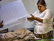 08 NOVEMBER 2015 - YANGON, MYANMAR: An elections worker starts the process of counting the votes at a polling place in Yangon. Elections workers counted the ballots at each polling place then called the results into the national elections office. It could be more than one week before the official results are completely tabulated. The citizens of Myanmar went to the polls Sunday to vote in the most democratic elections since 1990. The National League for Democracy, (NLD) the party of Aung San Suu Kyi is widely expected to get the most votes in the election, but it is not certain if they will get enough votes to secure an outright victory. The polls opened at 6AM. In Yangon, some voters started lining up at 4AM and lines were reported to long in many polling stations in Myanmar's largest city.    PHOTO BY JACK KURTZ