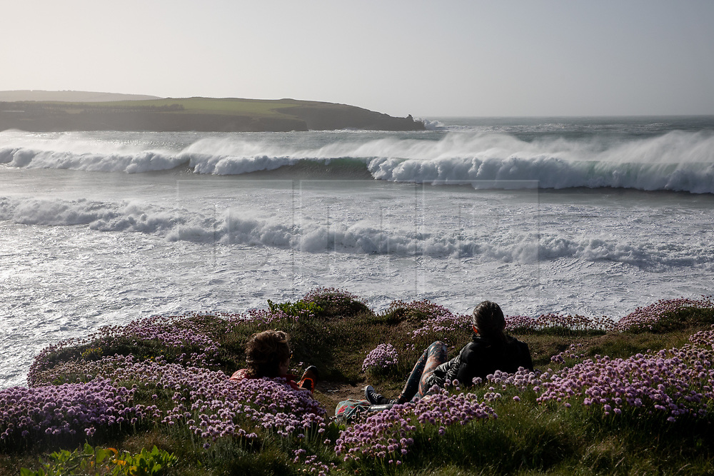 © Licensed to London News Pictures. 22/05/2020. Padstow, UK. A couple watch as huge waves of up to 15ft hit the coastline at Harlyn bay and the surrounding coves of North Cornwall. There is currently no RNLI Lifeguard service in the county due to Coronavirus (Covid-19), potentially causing issues as an unusual combination of large swell and warm weather is expected during the upcoming bank holiday weekend. Photo credit : Tom Nicholson/LNP