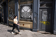As numbers of Covid-19 cases in Birmingham have increased dramatically in recent weeks, and with the expectation that the city will be added to the watch list of critical areas which may face a local lockdown, people wearing face masks pass street art of an angry face in the city centre on 18th August 2020 in London, United Kingdom. With other areas in the Midlands under localised lockdown, people and businesses are being urged to follow the Coronavirus advice for workplace and family life help reduce the risk.