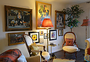 """The print of the Edouard Manet painting """"A Bar At the Folies-Bergere"""" is at top left on this wall in the living room, which features other scenes in France as well. Photo taken on January 8, 2019 for """"At Home"""" feature on Sandy Stolberg,  who uses dollar store finds as part of the decorations in her Belleville, IL condo.<br /> Photo by Tim Vizer"""