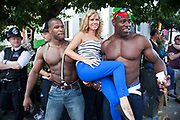 The 49th Notting Hill Carnival in West London. A celebration of West Indian / Caribbean culture and Europe's largest street party, festival and parade. Revellers come in their hundreds of thousands to have fun, dance, drink and let go in the brilliant atmosphere. Two muscular men pick up a woman to have her picture taken.
