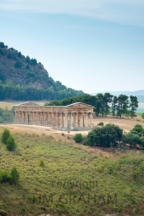 Tourists visiting the ancient ruins of the stone Doric Temple of Segesta in the landscape, Sicily, Italy