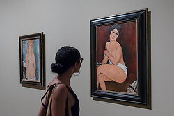 """© Licensed to London News Pictures. 21/11/2017. London, UK.  A visitor views (R) """"Seated Nude (La Belle Romaine)"""", 1917.  Preview of """"Modigliani"""", the most comprehensive exhibition of works by Amedeo Modigliani ever held in the UK.  On display are iconic portraits, sculptures and 12 nudes, the largest group ever shown in the UK.  The show runs 23 November to 2 April 2018.  Photo credit: Stephen Chung/LNP"""