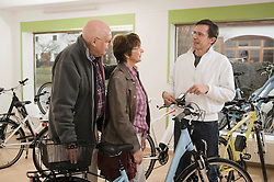 Senior couple taking advice from sales man about bicycle