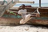 A girl on a makeshift swing on the beach at Nungwi, Zanzibar, Tanzania