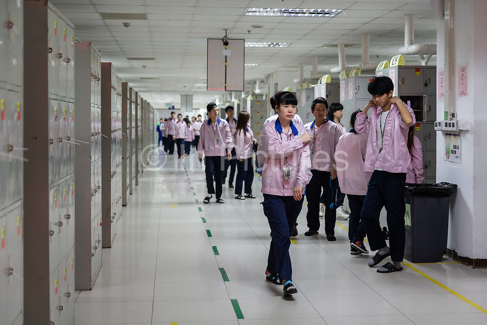 Employees make their way towards the assembly line area at a Pegatron Corp. factory in Shanghai, China, on Friday, April 15, 2016. This is the realm in which the worlds most profitable smartphones are made, part of Apple Inc.s closely guarded supply chain.
