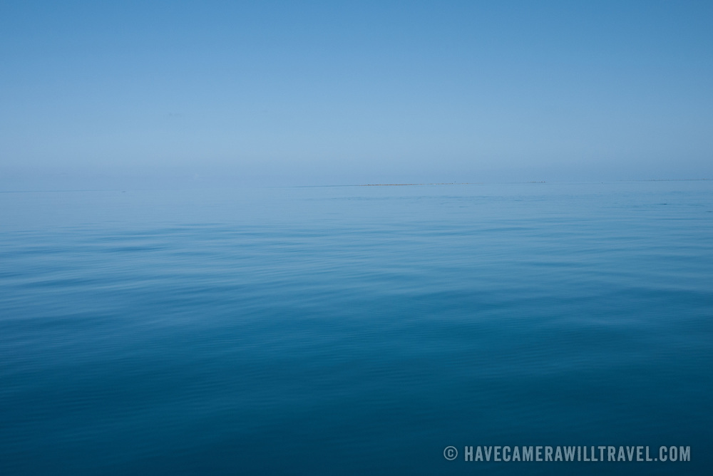 Becalmed seas on the Great Barrier Reef, Australia. The calm waters, reflecting the sky, make it hard to distinguish sea from sky with a near seamless horizon. This particular shot was taken about 150 miles northeast of Gladstone on Swains Reef, about 115 miles offshore.