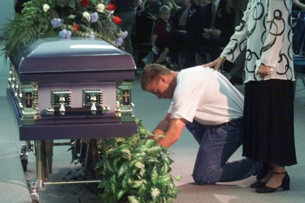 Littleton,Colorado,April 26, Nick Foss, injured in the Columbine shootings kneels at the casket of Columbine teacher Dave Sanders killed was trying to save students in the attack.  Photo by Rick Wilking