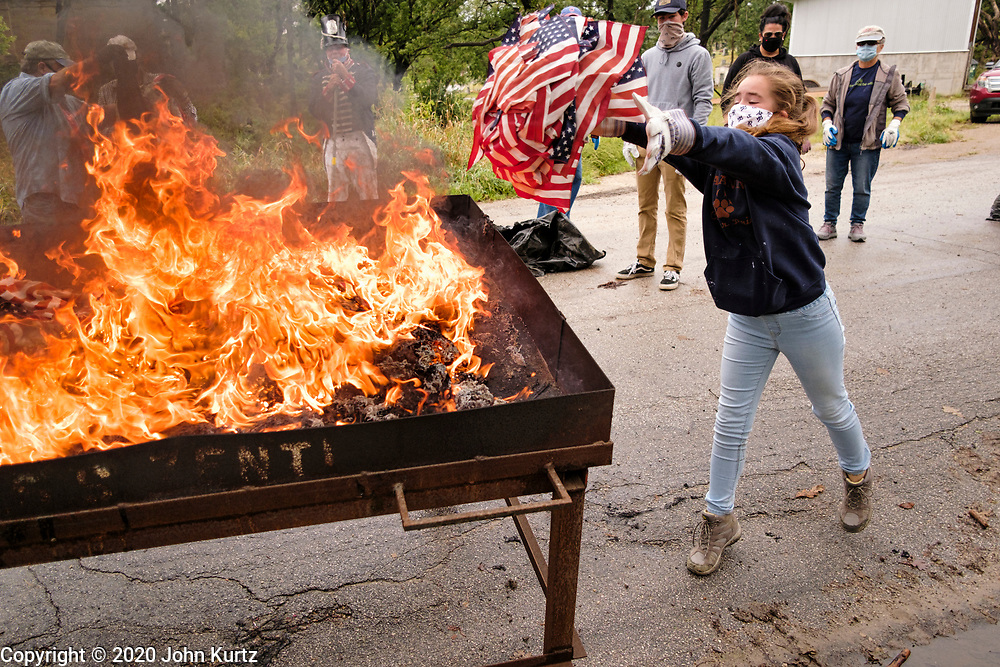 12 SEPTEMBER 2020 - DES MOINES, IOWA: SCARLETT BROWN throws US flags into the fire during a flag retirement ceremony at Glendale Cemetery in Des Moines. About 10 volunteers came to the cemetery Saturday morning to properly dispose of about 4,000 American flags. The flags had flown over veterans' graves, local businesses, and state offices. The US Flag Code calls for used American flags to be respectfully disposed of in a fire.   PHOTO BY JACK KURTZ