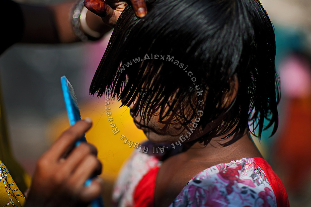 Sangita Jatev, 38, is brushing her daughter Poonam's hair while in the front yard of their newly built home in Oriya Basti, one of the water-contaminated colonies in Bhopal, central India, near the abandoned Union Carbide (now DOW Chemical) industrial complex, site of the infamous '1984 Gas Disaster'.