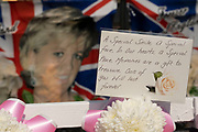 On the day after what would have been the 60th birthday of Princess Diana, people gather to pay their respects, and to lay flowers, pictures and messages at a memorial to her at the gates of Kensington Palace on 2nd July 2021 in London, United Kingdom. Diana, Princess of Wales became known as the Peoples Princess following her tragic death, and now as in 1997, many royalists, and mourners came to her royal residence in remembrance and respect.