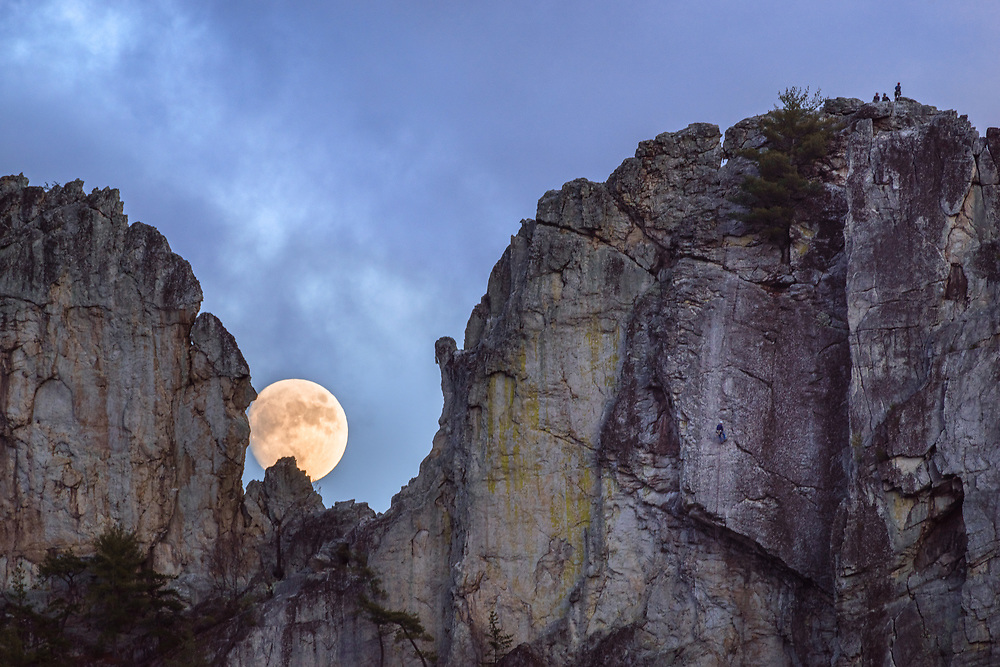 The moon rises in the Gunsight Notch at Seneca Rocks while climbers descend to the right.