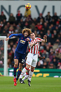 Marouane Fellaini of Man Utd (l)  jumps for a header with  Charlie Adam of Stoke city. Premier league match, Stoke City v Manchester Utd at the Bet365 Stadium in Stoke on Trent, Staffs on Saturday 21st January 2017.<br /> pic by Andrew Orchard, Andrew Orchard sports photography.