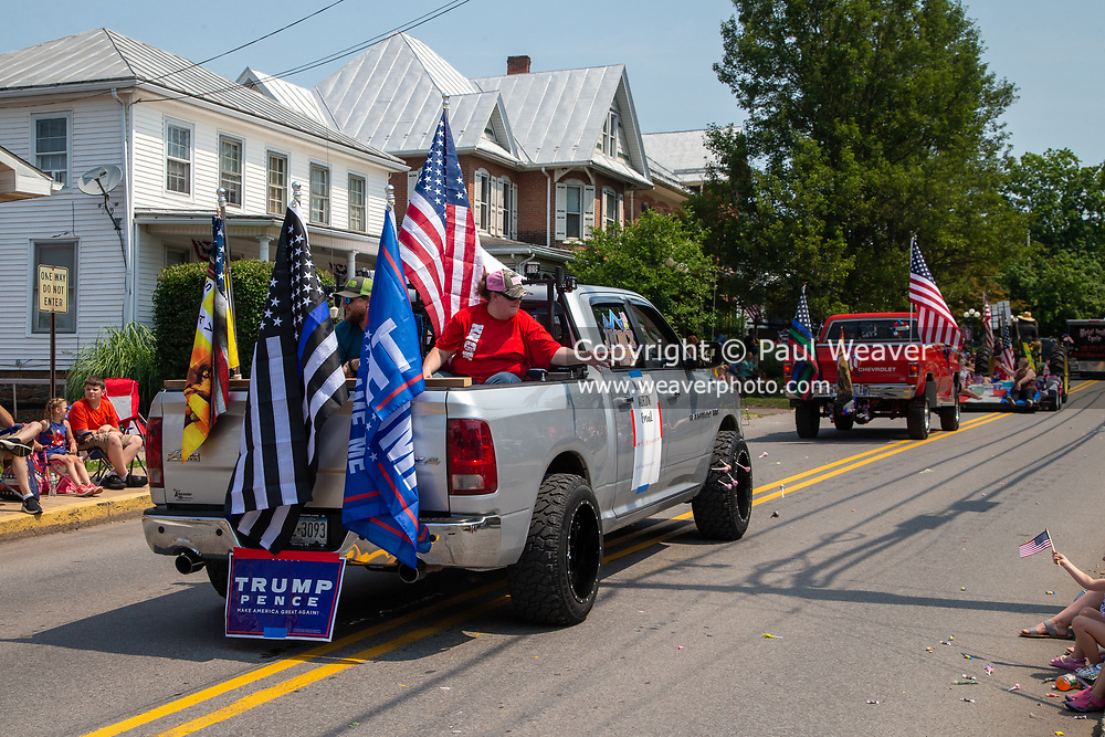 A woman throws candy from the back of a pickup truck in the Independence Day parade in Millville, Pennsylvania on July 5, 2021.