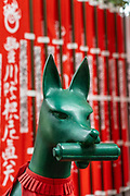 A statue of Inari Kitsune or fox goddess, wearing a red bib and surrounded by nobori banners at the Toyokawa Inari Betsuin temple in Asakusa, Tokyo, Japan. The Buddhist temple is part of the Soto Zen sect and enshrines the deity Toyokawa Dakinishinten but also known for the thousands of fox statues.