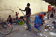 A homeless boy sweeps the pavement where he and his family will sleep, Karol Bagh, New Delhi, India.
