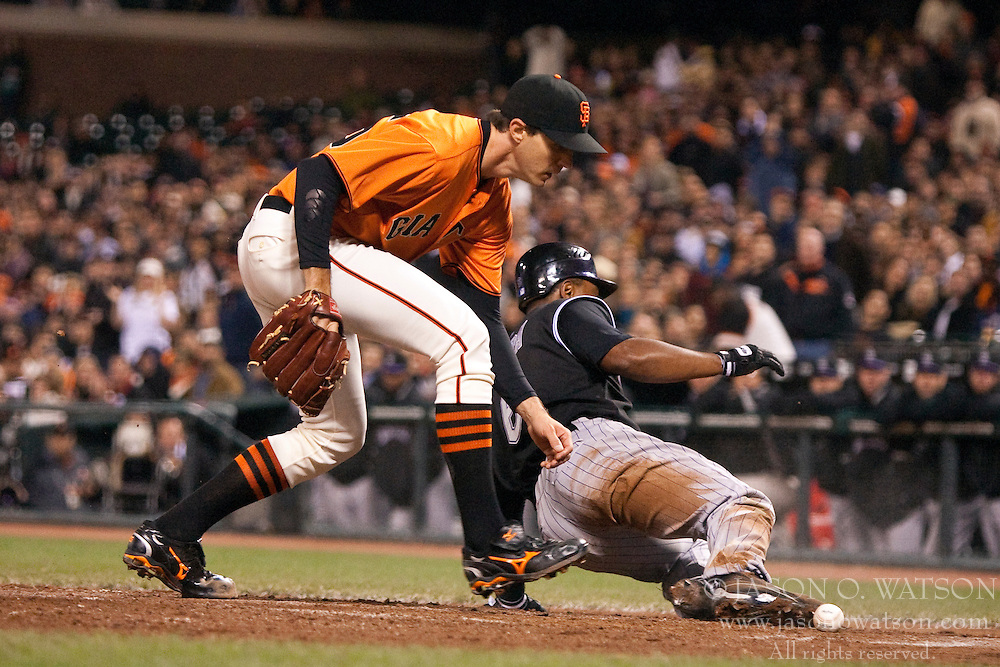 April 30, 2010; San Francisco, CA, USA;  Colorado Rockies second baseman Melvin Mora (6) slides into home plate past San Francisco Giants starting pitcher Barry Zito (75) to score a run on a wild pitch during the fifth inning at AT&T Park.  San Francisco defeated Colorado 5-2.