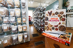 Book on Spice Blends and racks full of chiles and spices at Pendery's World of Chiles & Spices retail store, Fort Worth, Texas USA.