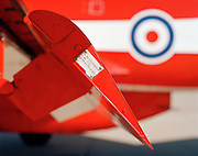 Seen in profile view, we are looking at the edge of a Hawk jet aircraft port wing flap set at about 45 degrees. Designed by BAE Systems and painted in the colour of the elite 'Red Arrows', Britain's prestigious Royal Air Force aerobatic team, at RAF Scampton, Lincolnshire. An original serial and issue numbers plate is riveted to its end assembly. The Hawk's classic, highly-efficient lifting wing is legendary with aeronatutical designer experts who recognise its ability to withstand excellent rates of climb and high g-forces (positive or negative gravity) routinely exerted on it by the Red Arrows team who fly more sorties (flights) and undergo more 'g' than other RAF squadron. In bright sunlight we see the graish red that is the signature colour of the team and the RAF's roundel is seen out of focus in the background to make a graphic engineering detail. .