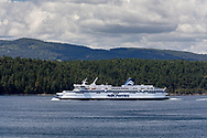 The BC Ferries ship Spirit of British Columbia (built in 1993) navigates Trincomali Channel on the way to Victoria (Swartz Bay) from Tsawwassen.  Photographed from Village Bay on Mayne Island, British Columbia, Canada.  Island in the background is Prevost Island (front) and Salt Spring Island behind.