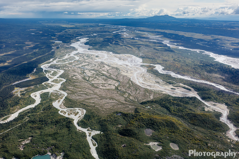 Aerial view of braided rivers flowing from glacial morain at foot of large glacier