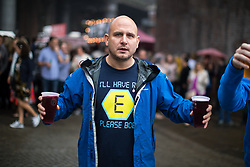 """© Licensed to London News Pictures . 01/07/2017 . Manchester , UK . A man wearing a Blockbusters """" E """" t-shirt in reference to the rave drug Ecstasy . Crowds enjoying the DJ sets ahead of the main act . Hacienda Classical play at the Castlefield Bowl as part of Sounds of the City , during the Manchester International Festival . A collaboration between DJs Mike Pickering and Graeme Park and the Manchester Camerata orchestra , Hacienda Classical reworks music by bands including the Happy Mondays and New Order and features Manchester musicians including Rowetta and Peter Hook . Photo credit : Joel Goodman/LNP"""
