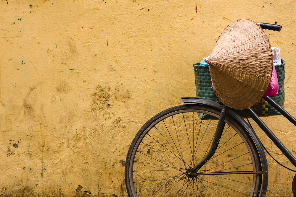 Close-up of a bicycle wheel and handlebars with a conical Non hat resting against a yellow wall, The Old Quarter, Hanoi City, Vietnam