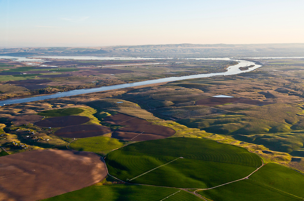 Aerial view of crop circles from center pivot irrigation systems along the Snake River just before it joins the Columbia River at Tri-Cities, Washington.<br /> (Kennewick, Pasco, and Richland) with Columbia River Confluence in background. Licensing - Open Edition Prints