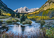 The Maroon Bells and yellow aspen leaves reflect in Maroon Creek after sunrise. The Maroon Bells are two adjacent peaks of the Elk Mountains: Maroon Peak 14,163 feet on left, seen behind North Maroon Peak 14,019 feet, in Maroon Bells-Snowmass Wilderness of White River National Forest. The mountains are on the border between Pitkin County and Gunnison County, 12 miles southwest of Aspen, in Colorado, USA.