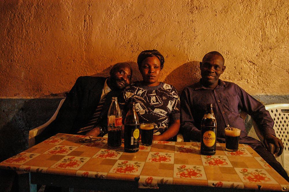 People drinking Guinness in a shebeen in Kibera.